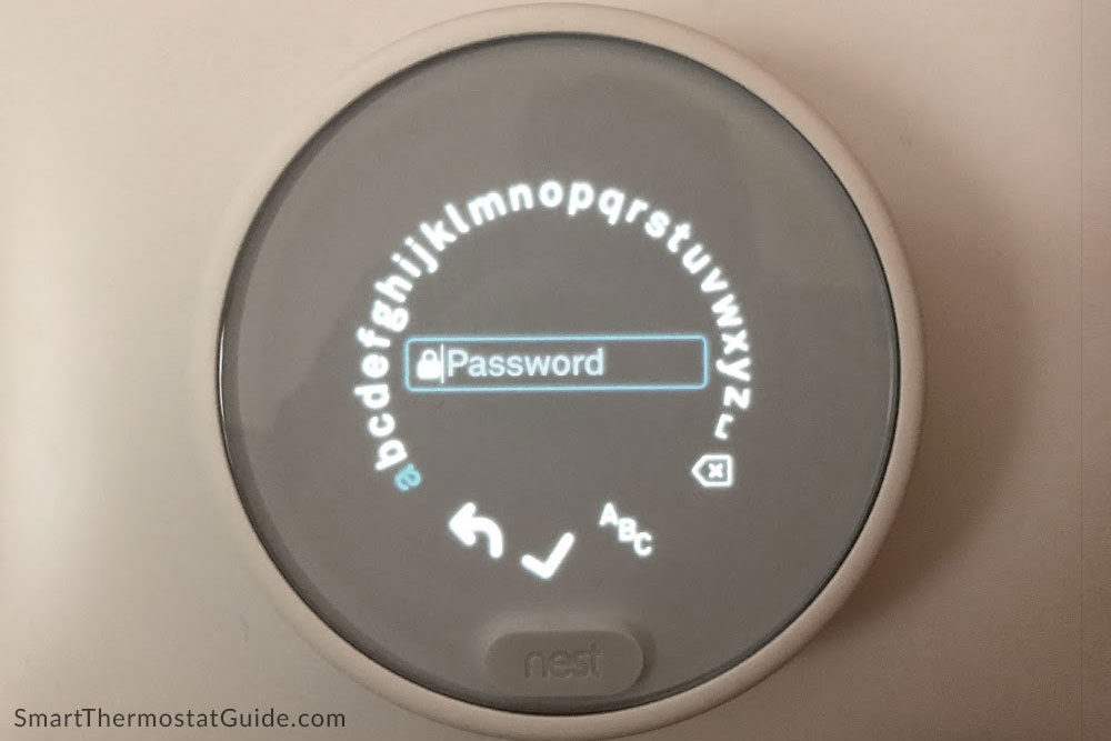 "Photo of Nest Thermostat E on ""enter WiFi password"" screen. Each letter must be cycled to and ""clicked"" on using the twist ring."