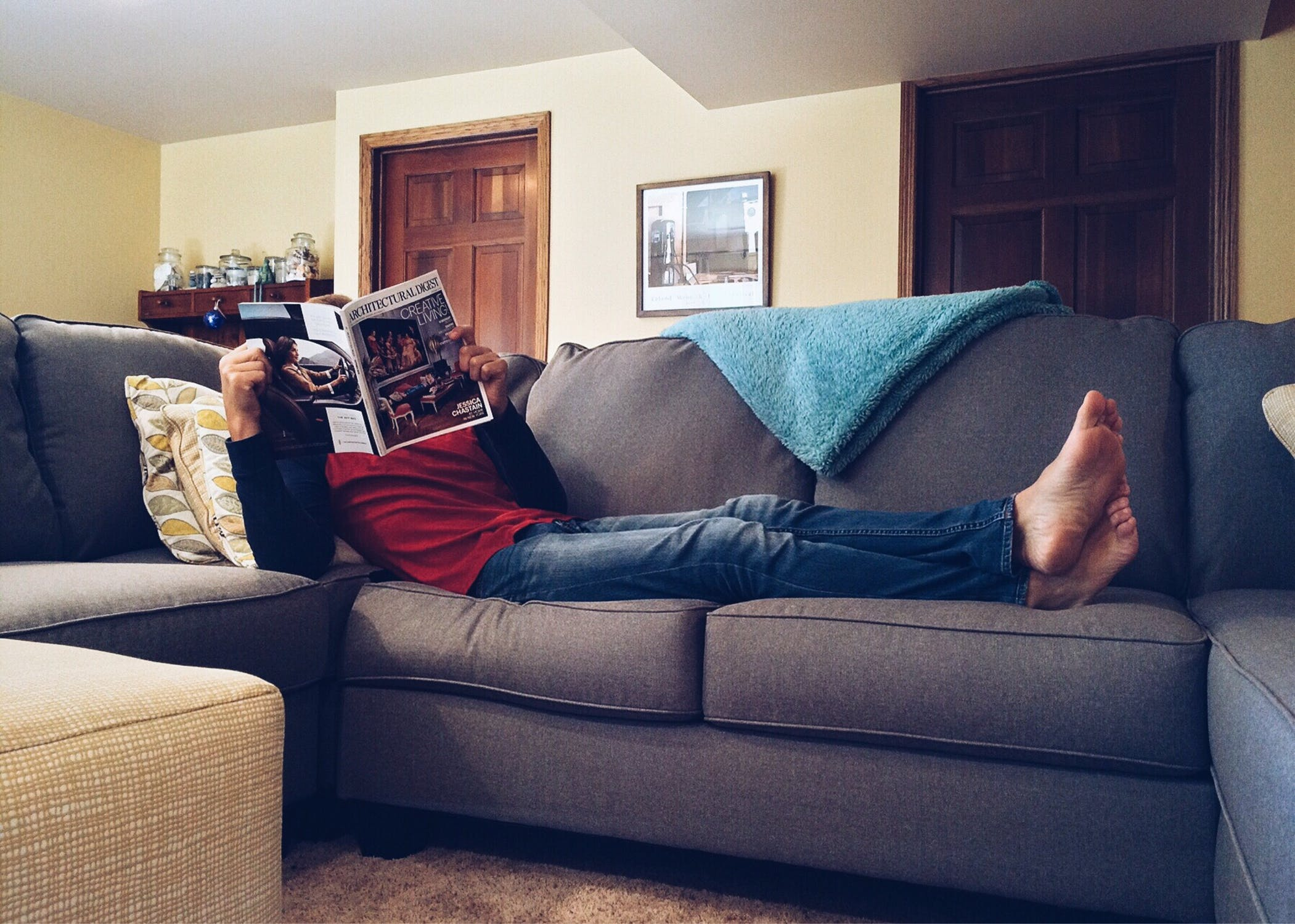 A person laying on a sofa in a living room