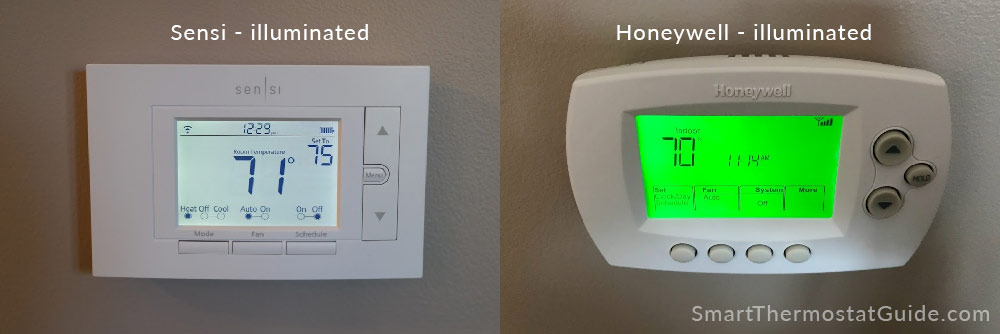 Sensi thermostat and Honeywell thermostat with illuminated screens. The Sensi's is a soft white, the Honeywell's is a bright green.