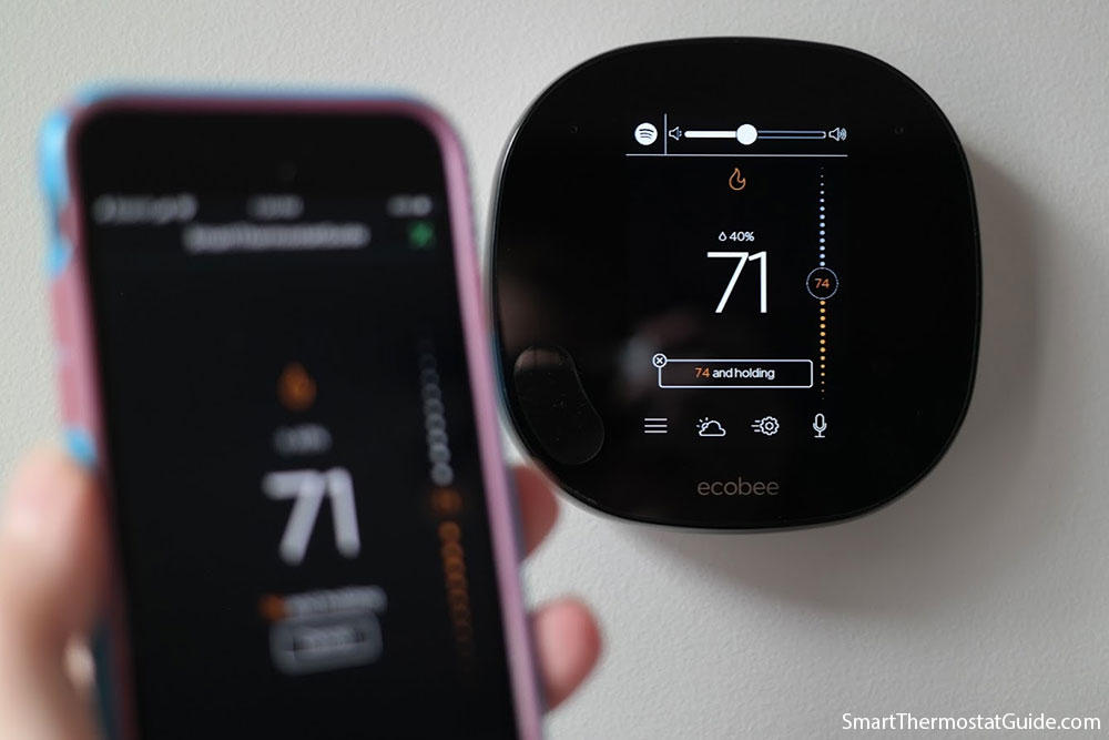 "Photo of the Ecobee SmartThermostat playing a song on Spotify. The thermostat displays a ""Spotify"" icon and volume control bar."